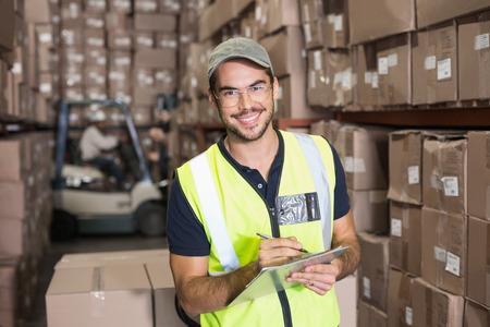 Warehouse worker smiling at camera with clipboard in a large warehouse photo