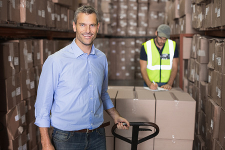 Warehouse manager smiling at camera with trolley in a large warehouse photo