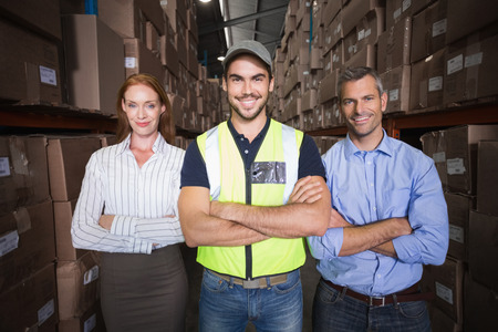 warehouse: Warehouse team smiling at camera showing thumbs up in a large warehouse Stock Photo