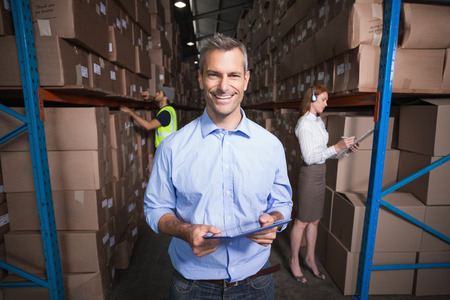 Warehouse manager smiling at camera in a large warehouse photo
