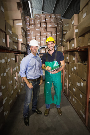 Warehouse manager smiling at camera with worker in a large warehouse photo