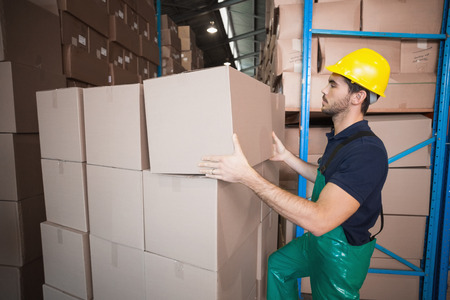 warehouse worker: Warehouse worker loading up a pallet in a large warehouse