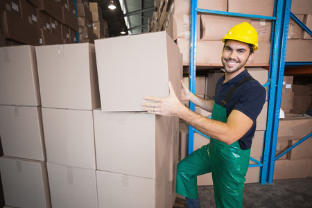 Warehouse worker loading up a pallet in a large warehouse photo