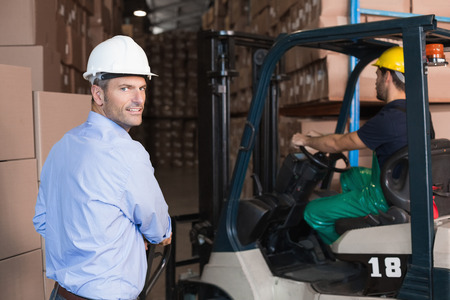 Warehouse manager smiling at camera with delivery in background in a large warehouse photo