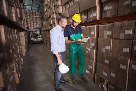 Warehouse manager talking with worker in a large warehouse photo