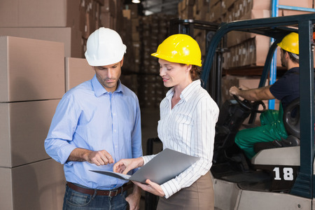 Warehouse manager talking with colleague in a large warehouse photo