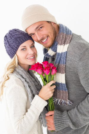 Attractive young couple in warm clothing holding flowers over white background photo