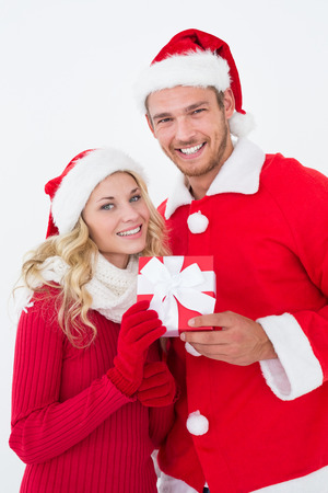 Portrait of attractive young couple wearing santa hats with gift over white background photo