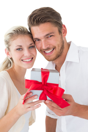 Attractive young couple holding gift over white background photo