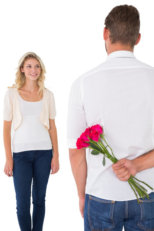 Man hiding bouquet of roses from young woman over white background photo