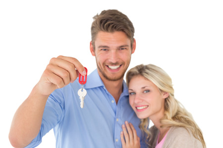 Portrait of happy attractive young couple holding new house key over white background photo