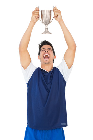 football trophy: Football player holding up winners cup over white background
