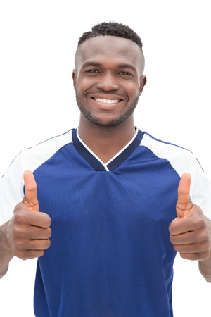 player: Portrait of a football player gesturing thumbs up over white background