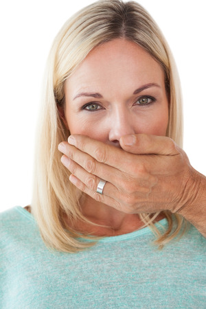 Close up of hand covering young womans mouth over white background