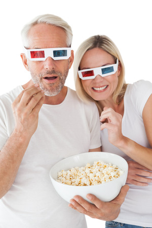 Happy mature couple wearing 3d glasses eating popcorn over white background photo