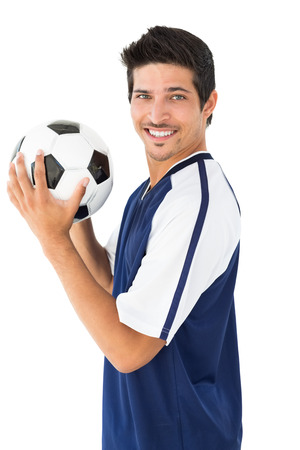 Smiling football player standing over white background photo