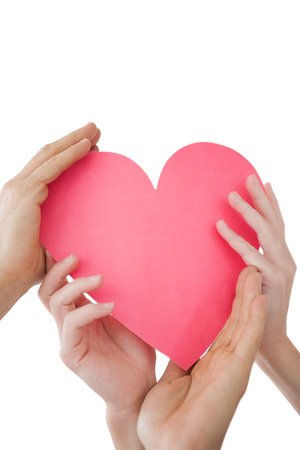 Close up of hands holding heart over white background Stock Photo