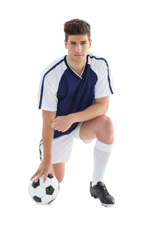 football world cup: Portrait of a serious football player over white background