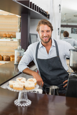 coffee machines: Handsome barista smiling at camera at the coffee shop