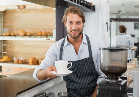 mesero: Barista hermoso que ofrece una taza de caf� a la c�mara en la cafeter�a Foto de archivo