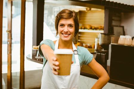 mujeres trabajando: Sonriendo a la cámara sosteniendo vaso desechable en la cafetería Pretty barista Foto de archivo