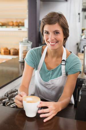 Pretty barista offering cup of coffee smiling at camera at the coffee shop photo