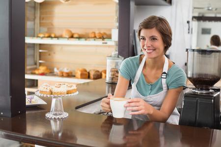 Jolie barista offre tasse de café en souriant à la boutique de café Banque d'images - 31949707