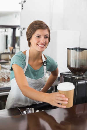 Pretty barista holding disposable cup at the coffee shop photo