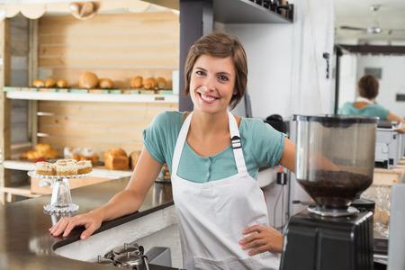 Jolie barista souriant à la caméra à la boutique de café Banque d'images - 31343645