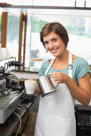 Pretty barista pouring milk into cup of coffee at the coffee shop photo