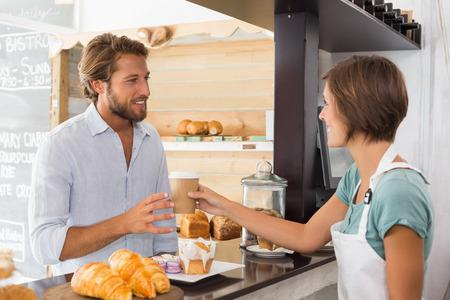Hübsche Kellnerin serviert glücklichen Kunden in der Cafeteria