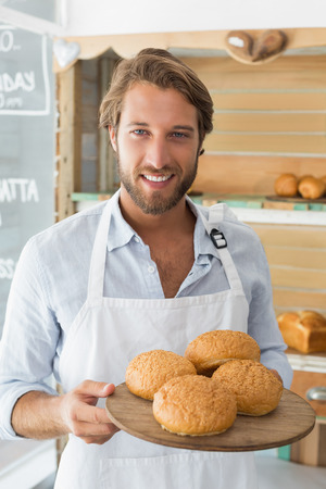 Handsome waiter holding tray of bread rolls at the coffee shop photo