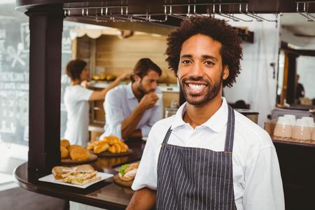 コーヒー ショップでカメラに微笑んでハンサムなウエーター