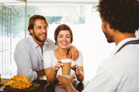 Barista serving two happy customers at the coffee shop photo