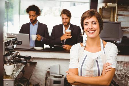 Pretty barista glimlachen op de camera in de koffieshop Stockfoto