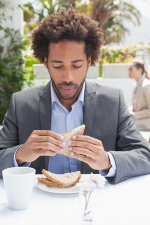 18 to 30s: Businessman having sandwich for lunch outside at the coffee shop