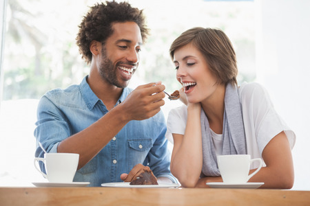 woman eating cake: Casual couple having coffee together at the coffee shop Stock Photo