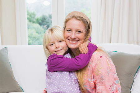 18 to 30s: Happy mother and daughter on the couch at home in the living room Stock Photo