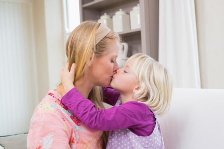blonde females: Happy mother and daughter on the couch at home in the living room Stock Photo