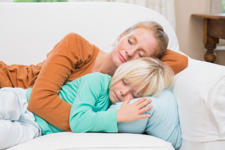 some under 18: Happy mother and daughter napping on the couch at home in the living room