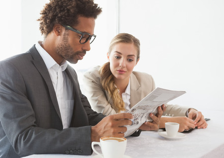 well read: Business people having coffee looking at newspaper at the coffee shop Stock Photo