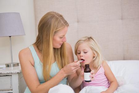 ni�os enfermos: Linda ni�a enferma siendo cuidado en casa en el dormitorio Foto de archivo