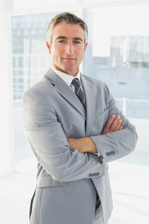 business men: Businessman looking at the camera with his arms folded Stock Photo