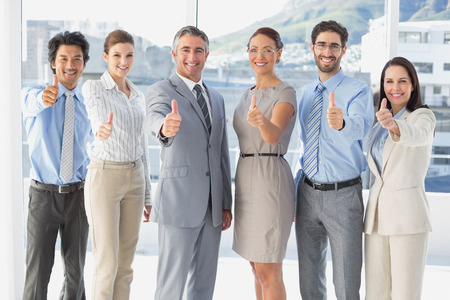 Employees giving a thumbs up at work photo