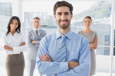 18 to 30s: Smiling businessman and his co-workers standing behind Stock Photo