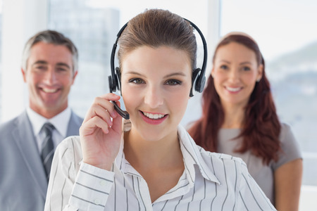 18 30s: Businesswoman wearing a work headset with fellow employees Stock Photo