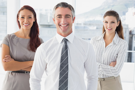 18 to 30s: Smiling businessman with his co-workers in an office