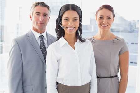 Businesswoman wearing a work headset with fellow employees photo