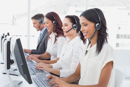 Employees typing on their computers using headsets