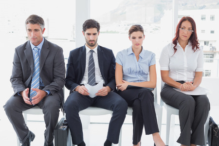 Business people sitting in a row in an office photo